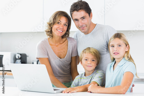 Smiling family with laptop