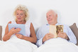 Old couple reading and using a tablet