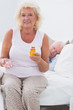 Old woman with an opened pill bottle