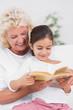 Granddaughter and grandmother reading a novel together