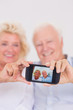 Aged couple taking pictures with smartphone