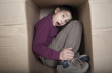 Teenage boy hiding in cardboard box