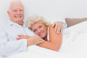 Cheerful couple lying on the bed