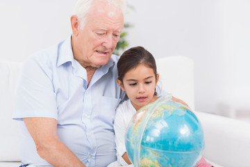 Granddaughter and grandfather with globe