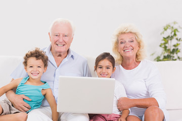 Smiling grandparents with children using a pc