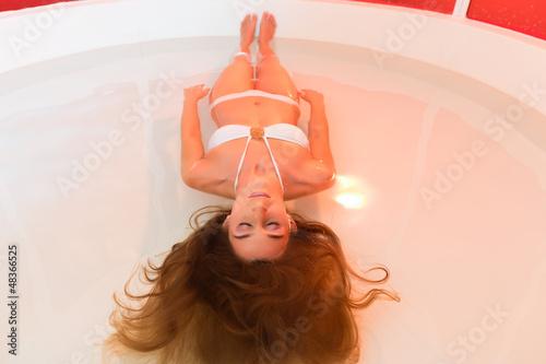 Wellness - junge Frau beim Floaten im Wasser
