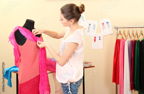 beautiful young dressmaker in workroom