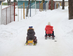Little boy and girl  slides down from the snow hill on a sledge