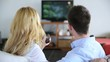 Couple in sofa choosing tv program