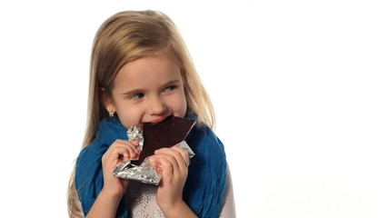 little girl a blonde eats a chocolate