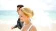 Bride and groom walking on a sandy beach