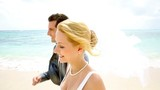 Bride and groom walking on a sandy beach