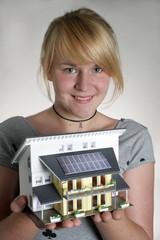 Maedchen haelt ein Modellhaus mit Sonnenkollektoren