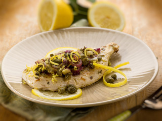 chicken with capers onions and lemon peel, selective focus