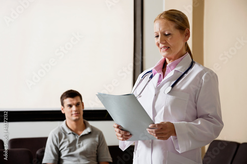 Female Doctor Looking At File