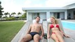 Couple relaxing in long chairs by swimming-pool