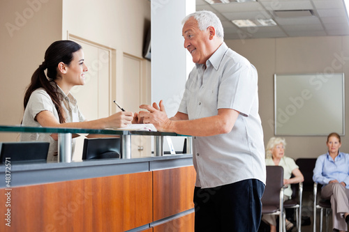 Man Communicating With Female Receptionist