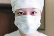 Close-up portrait of Chinese woman wearing a surgical mask.