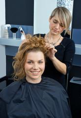 hair stylist curling woman hair