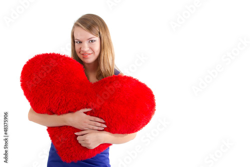 Young beautiful girl hugs a big soft heart