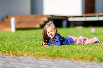 Outdoor portrait of cute little girl lying on the meadow