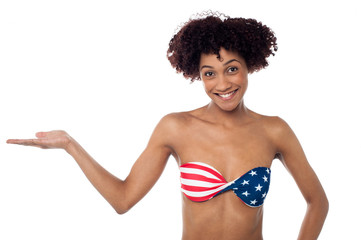 Smiling model in stars and stripes bikini presenting copy space