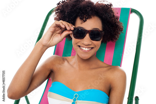 Relaxing female model adjusting her shades