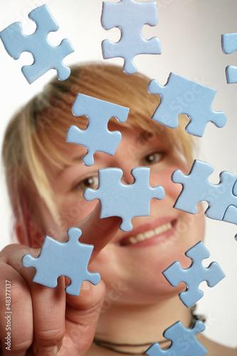 Leinwanddruck Bild Junge Frau legt Puzzle-Teile zusammen
