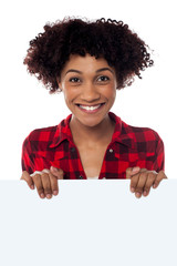 Smiling woman standing behind blank whiteboard