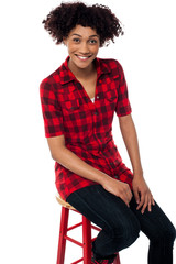 Curly haired fashion model sitting on red stool