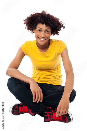 Smiling lady sitting legs crossed on the floor