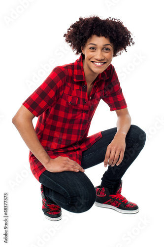 Smiling female model in squatting posture