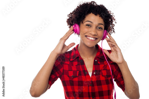 Smiling woman with pink headphones on