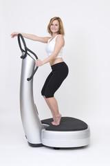 Sportliche schlanke Frau trainiert stehend auf Powerplate