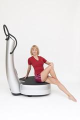 Junge sportliche Frau trainiert sitzend auf einer Powerplate