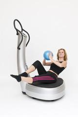 Junge sportliche Frau sitzend mit Ball auf Powerplate