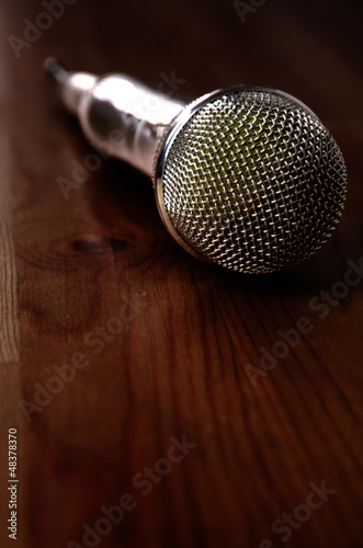 Microphone on wooden background