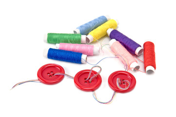 Red buttons and thread spools  on white background