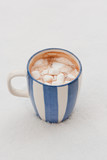 Cup of hot chocolate with melted marshmallows on snow