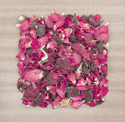 Dried rose petal pot-pourri on wooden background