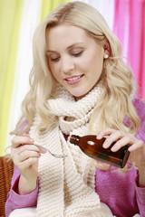 Hübsche Frau zählt Tropfen aus einer Arzneiflasche ab