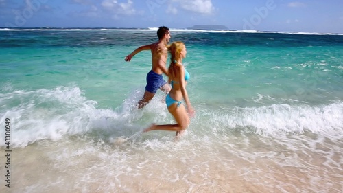 Couple running on sandy beach in caribbean island