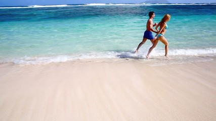 Cheerful couple running in crystal clear water