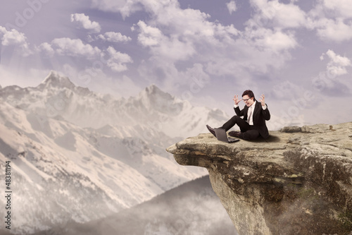 Happy businessman on top of mountain