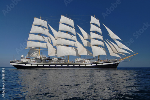 Sailing frigate under full sail in the ocean - 48381536