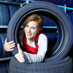 Female apprentice for mechanic shows thumb up for tire changing