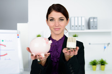 businessfrau mit sparschwein und thermostat