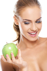 Happy woman with a crisp green apple