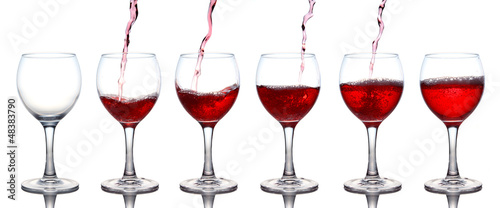 Pouring of red wine in a glasss isolated on white