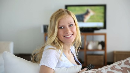 Blond woman at home watching tv
